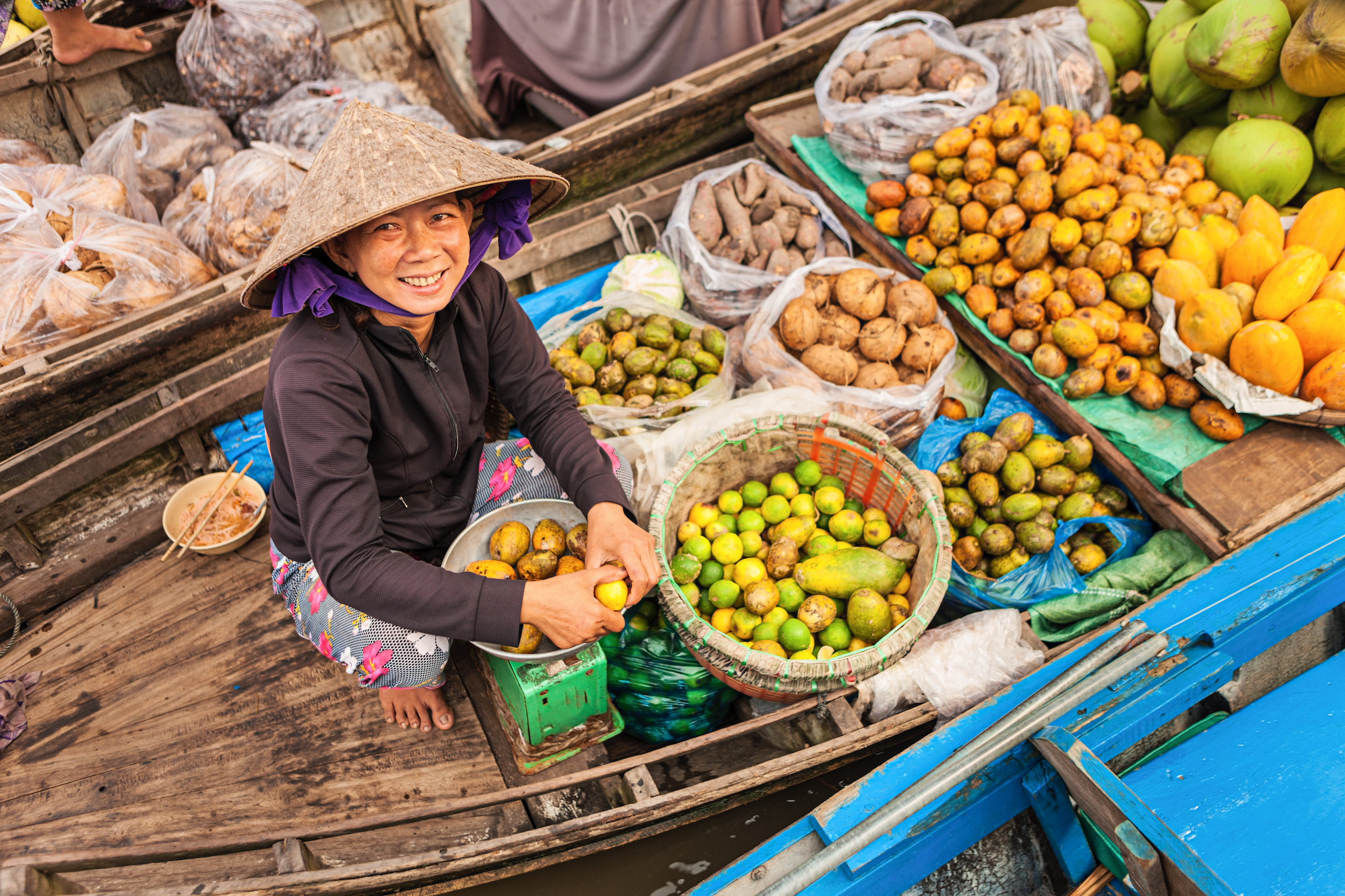 A lady with her boat filled with seasonal fruits
